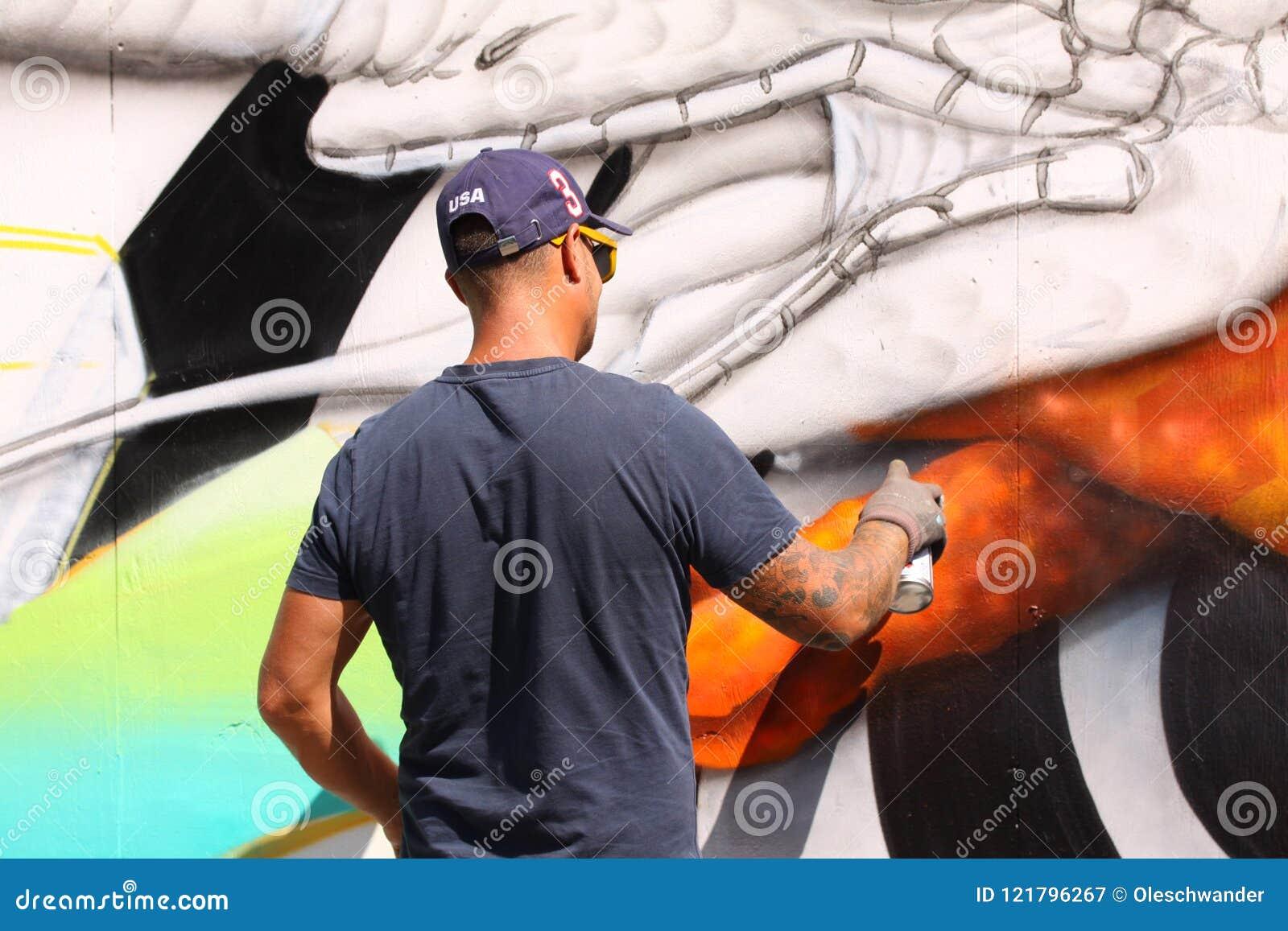 Artiste de rue peignant le graffiti coloré sur le mur - concept d art moderne avec les murales vivants de peinture urbaine de typ