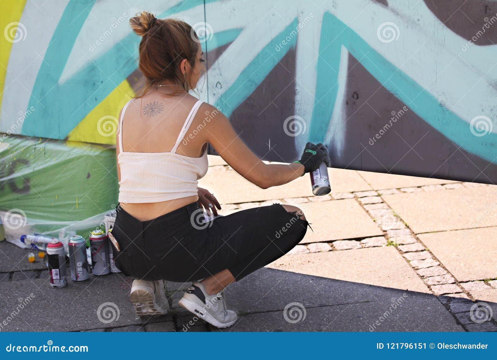 Artiste féminin de rue peignant le graffiti coloré sur le mur - concept d art moderne avec les murales vivants de peinture urbain