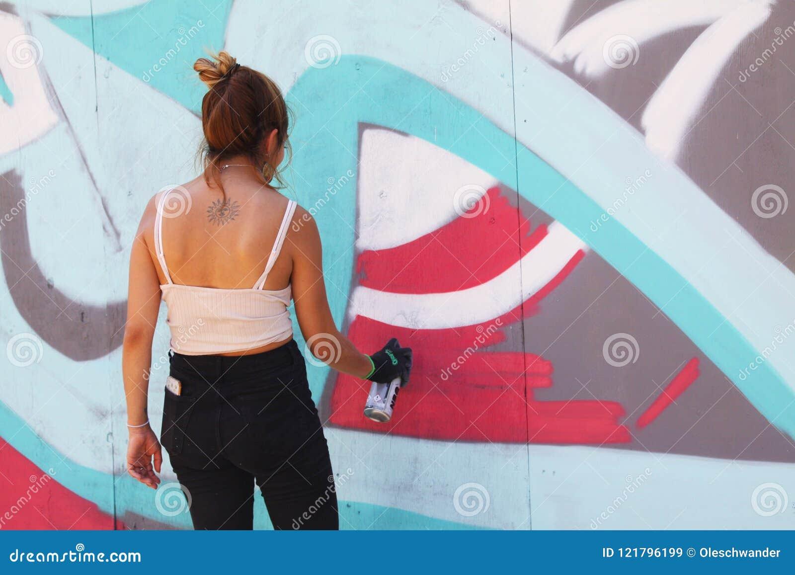 Artiste Féminin De Rue Peignant Le Graffiti Coloré Sur Le