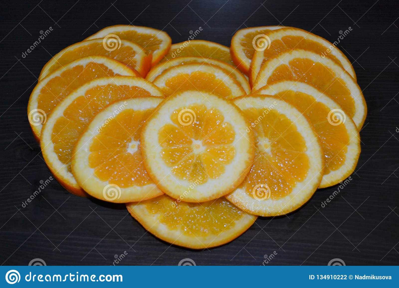 Artistic composition of slices of ripe oranges posed in a shape of a heart on wooden background.