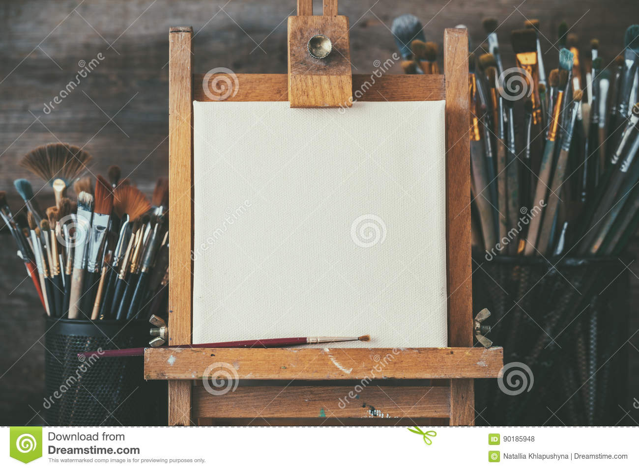 Artistic equipment in a artist studio: empty artist canvas and brushes.