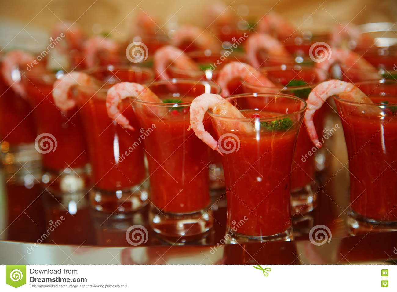Artistically decorated drink of tomato with vodka and shrimp - is a delicacy from the chef - a dish of venison.