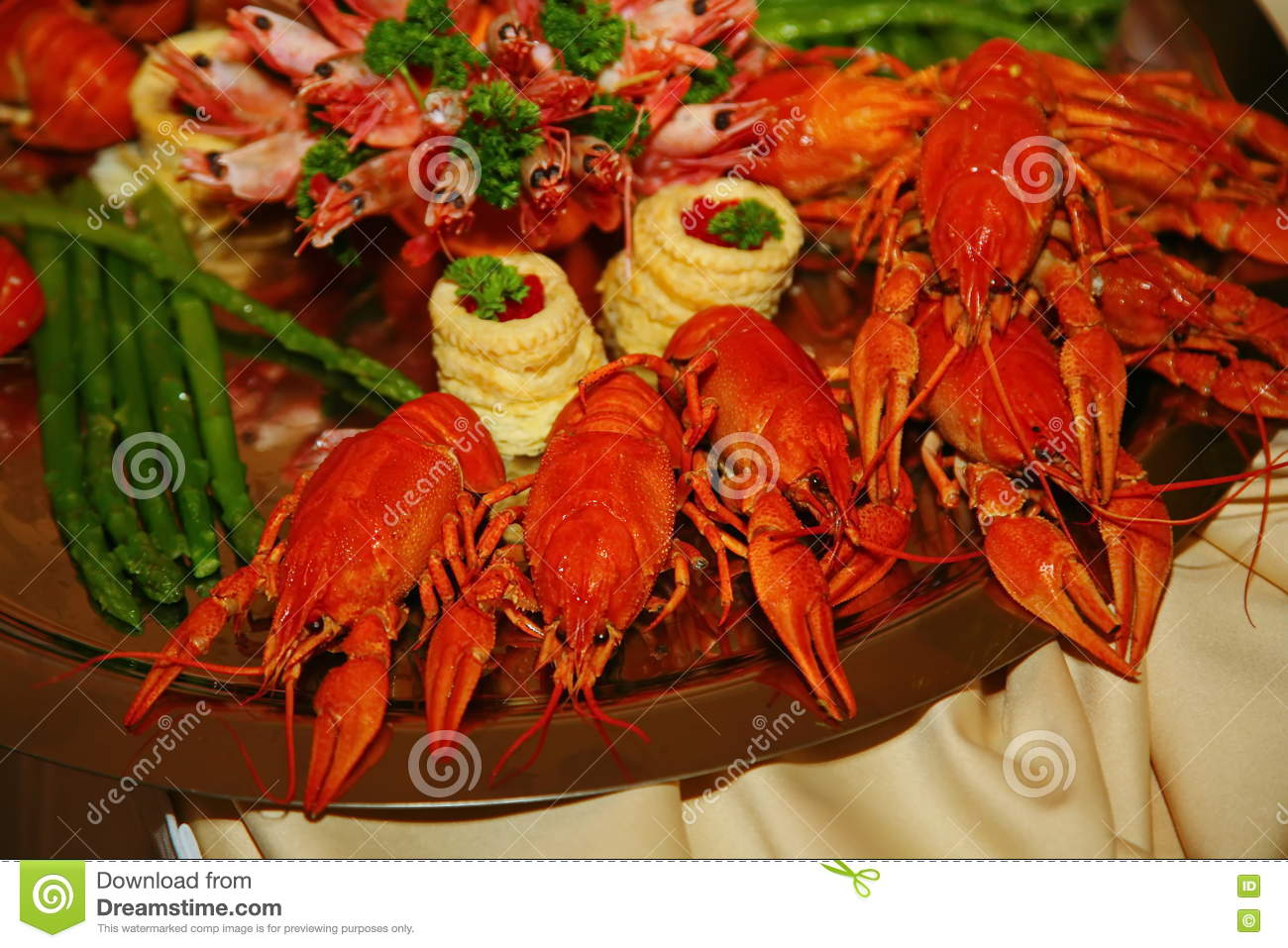 Artistically decorated with red boiled cancer with asparagus and prawns is a delicacy from the chef - a dish of venison.