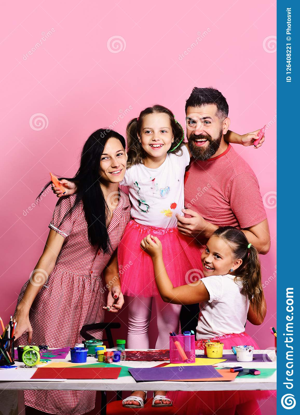 Artists family hugs on pink background. Creativity and family concept