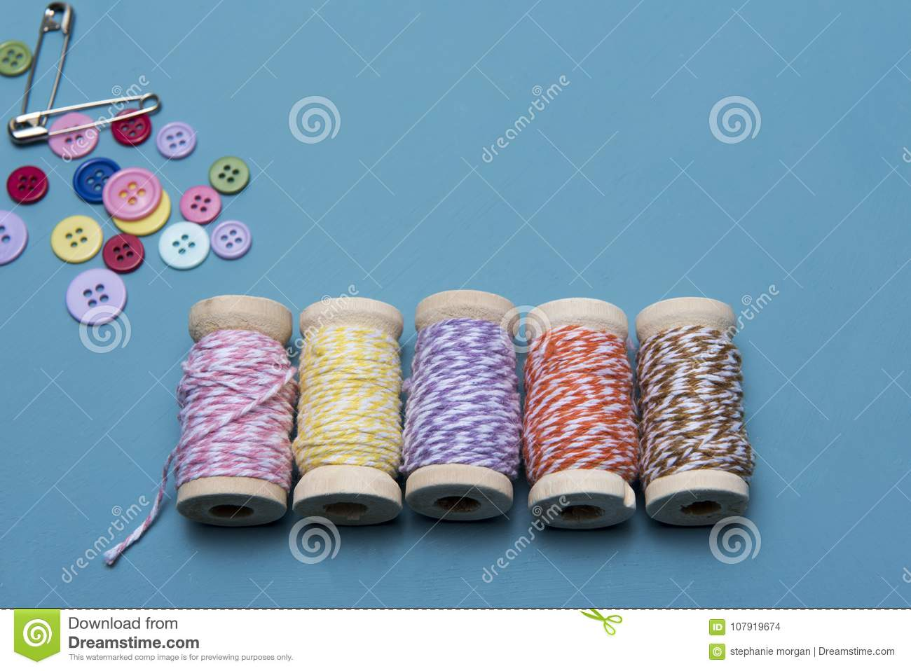Arts and crafts background image of colourful string with pins and buttons