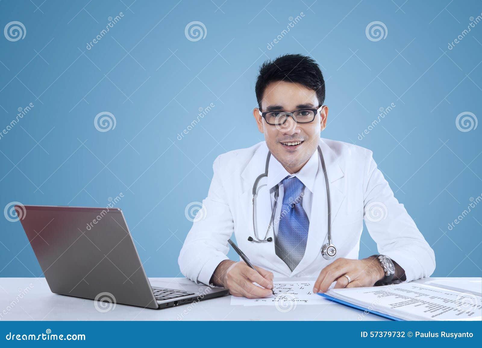 Arts die aan bureau over blauwe achtergrond werken