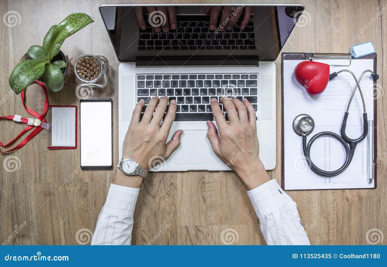 Arts die bij bureau werken en een laptop computer met behulp van