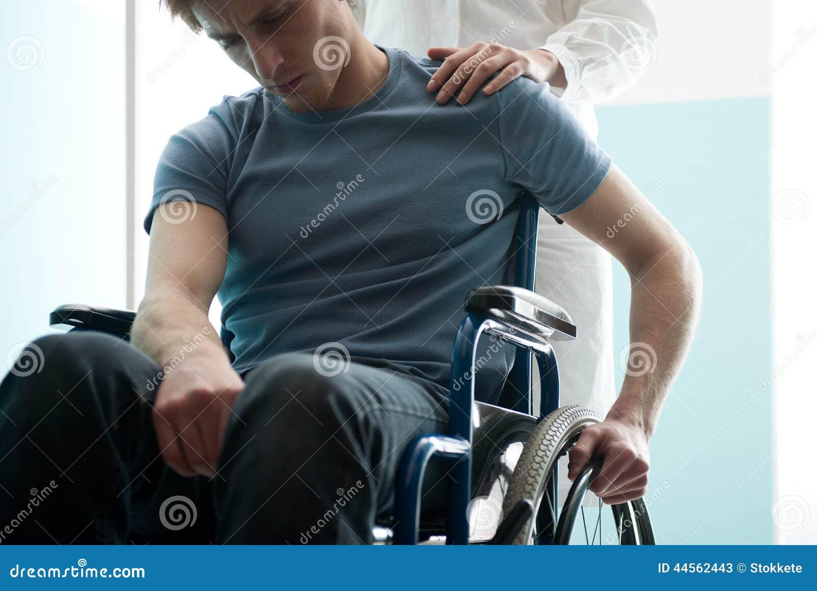 Arts die jonge mensenzitting in rolstoel troosten