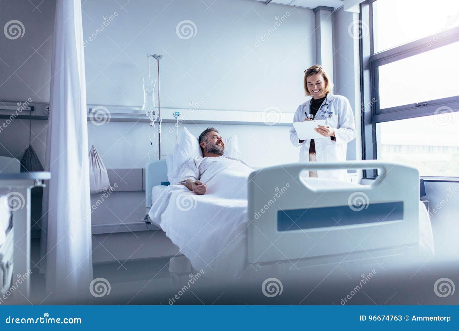 Arts die zieke patiënt in het ziekenhuisbed bijwonen