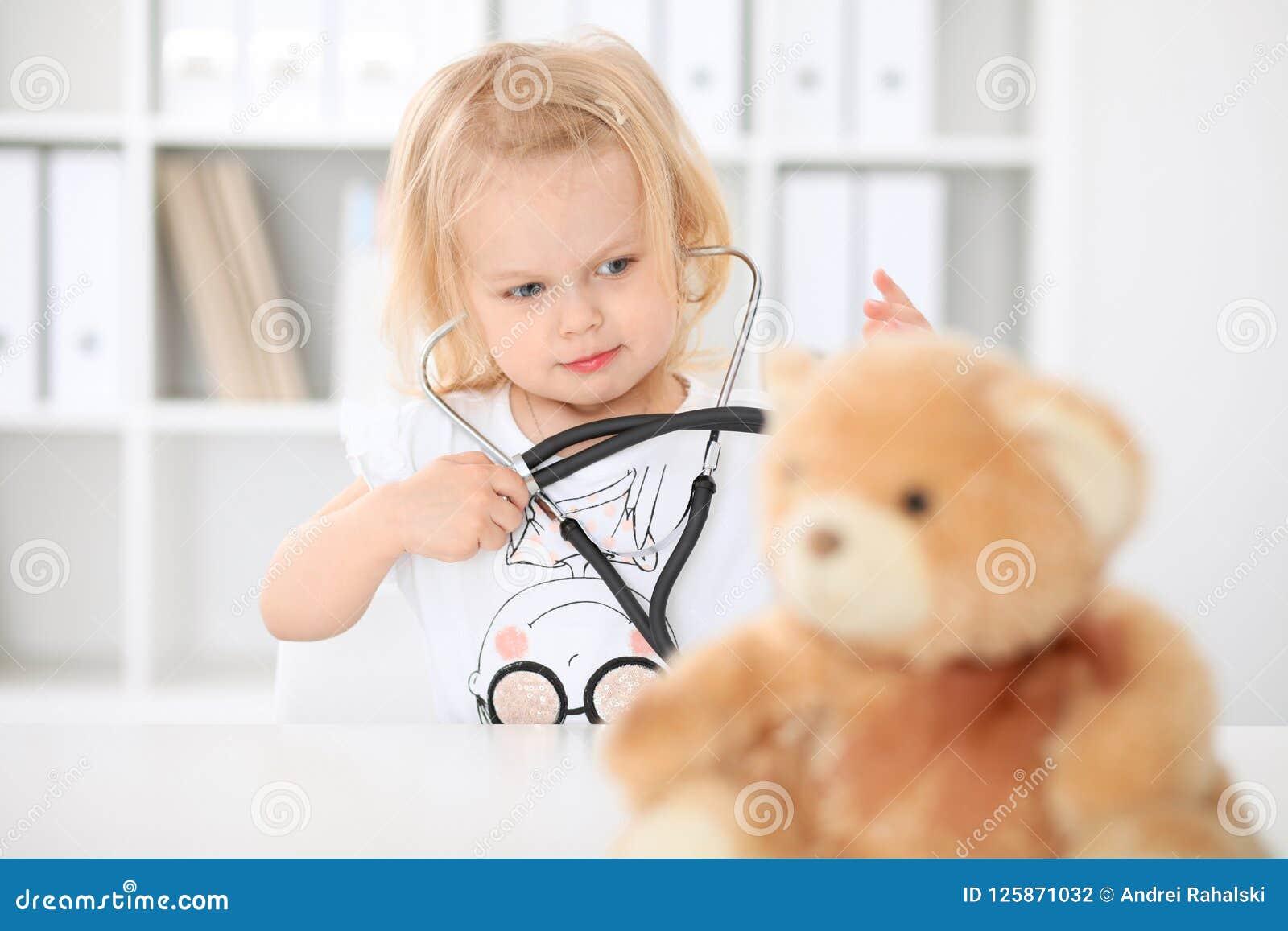 Arts en patiënt in het ziekenhuis Meisje die teddybeer met stethoscoop onderzoeken Gezondheidszorg, verzekering en hulp