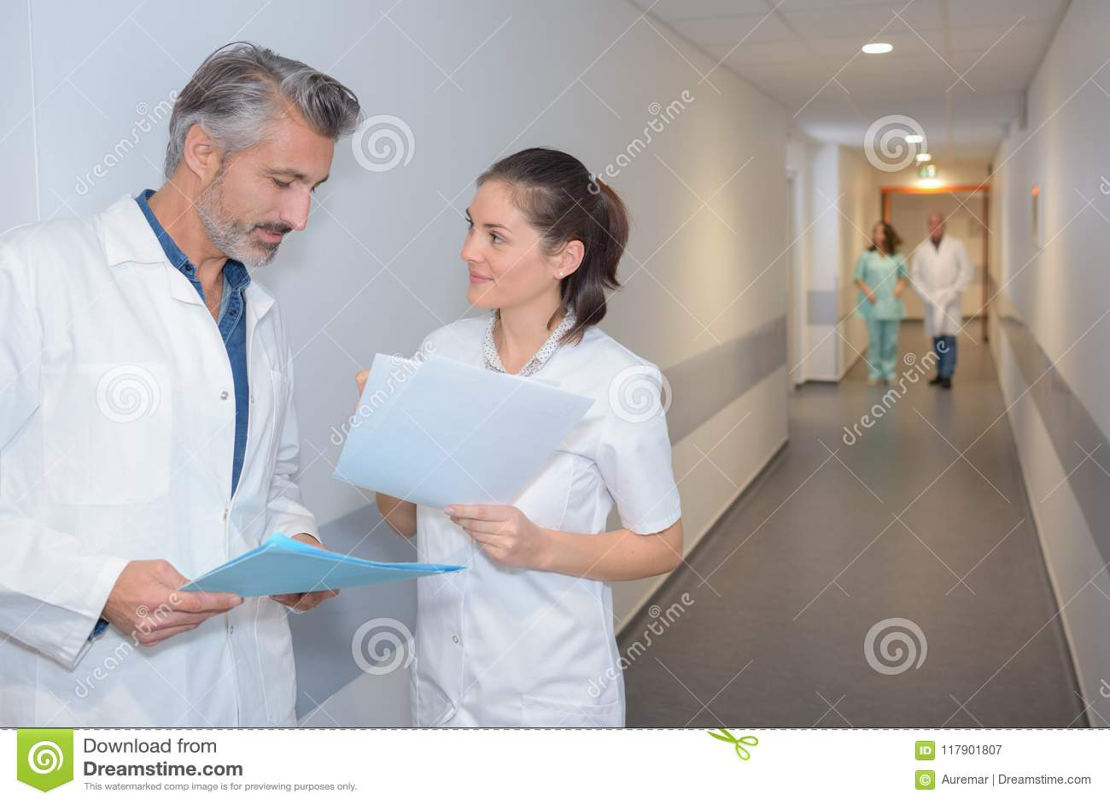 Artsen die nota s in het ziekenhuisgang bekijken