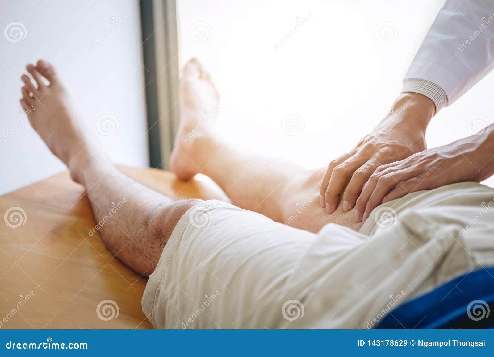 Artsenfysiotherapeut die een mannelijke patiënt bijstaan terwijl het geven uitoefenend behandeling die het been van patiënt in ee