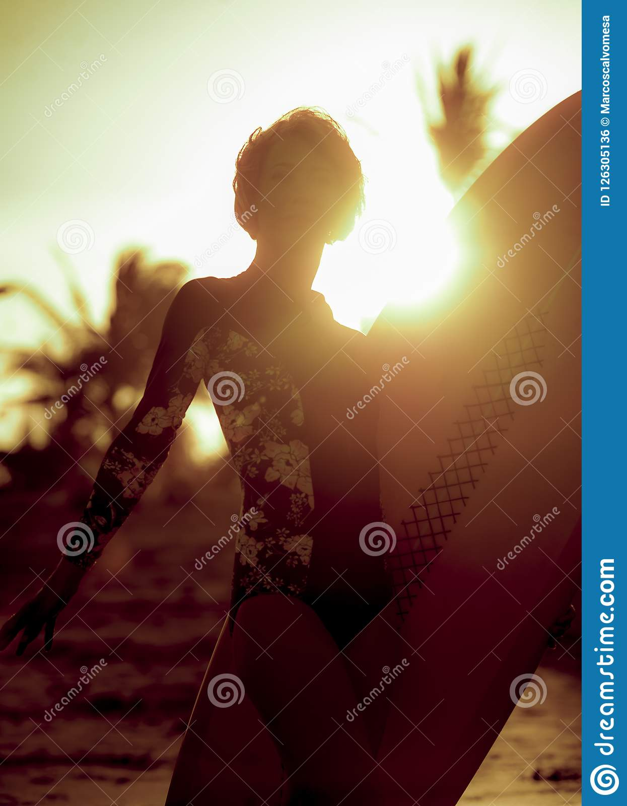 Arty silhouette with sun lens flare of young happy and attractive surfer girl carrying surf board posing on extreme backlight enjo