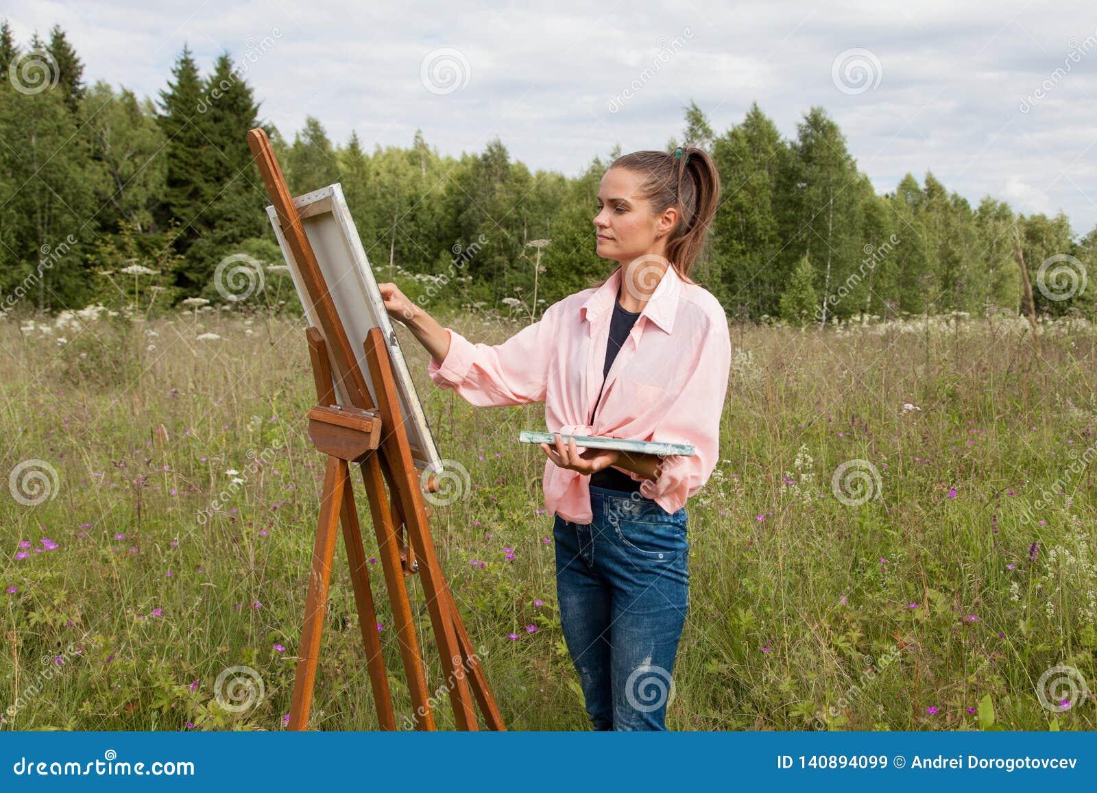 Artysta maluje obrazek w polu