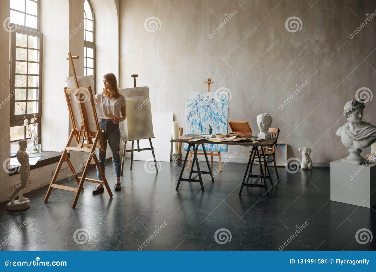 Artysta przy pracującym procesem Młoda kobieta tworzy obraz Warsztatowy pokój z lekkimi i klasycznymi rzeźb popiersiami