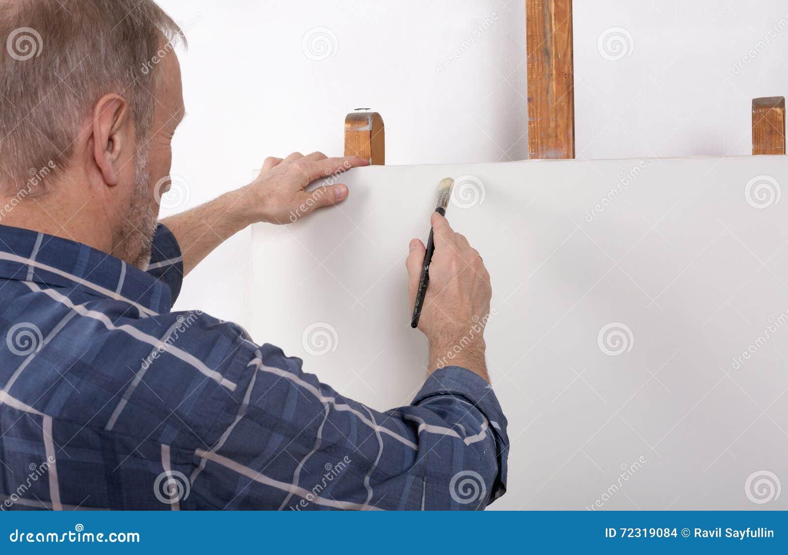 Artysta w pracownianym główkowaniu przed białą kanwą