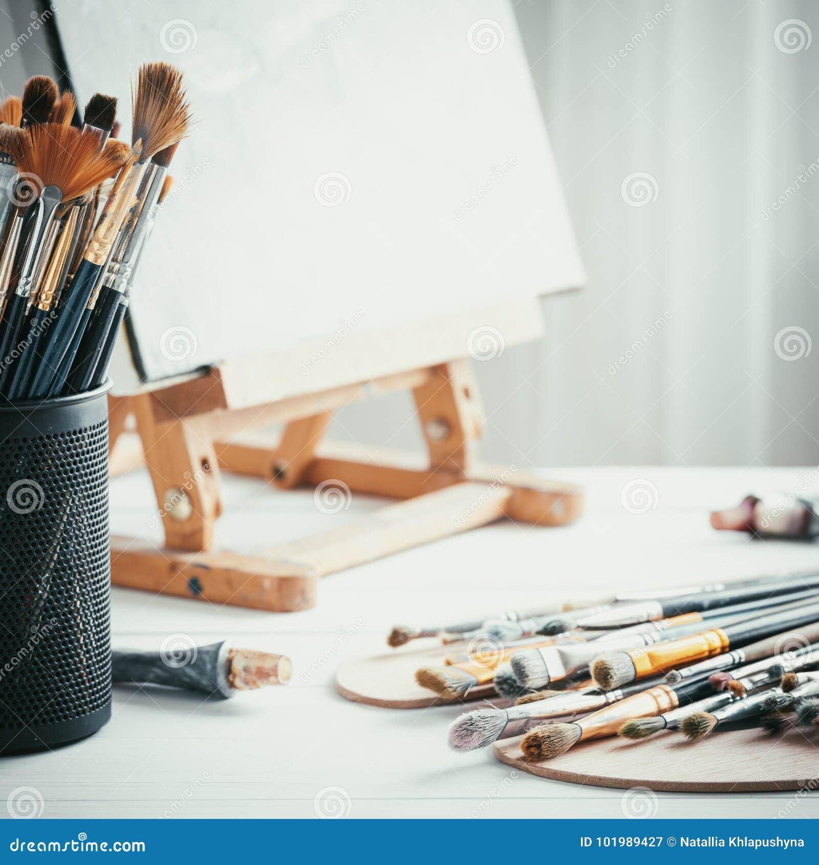Artystyczny wyposażenie w malarza studiu: sztaluga, farb muśnięcia, tubki farba, paleta i obrazy na praca stole,
