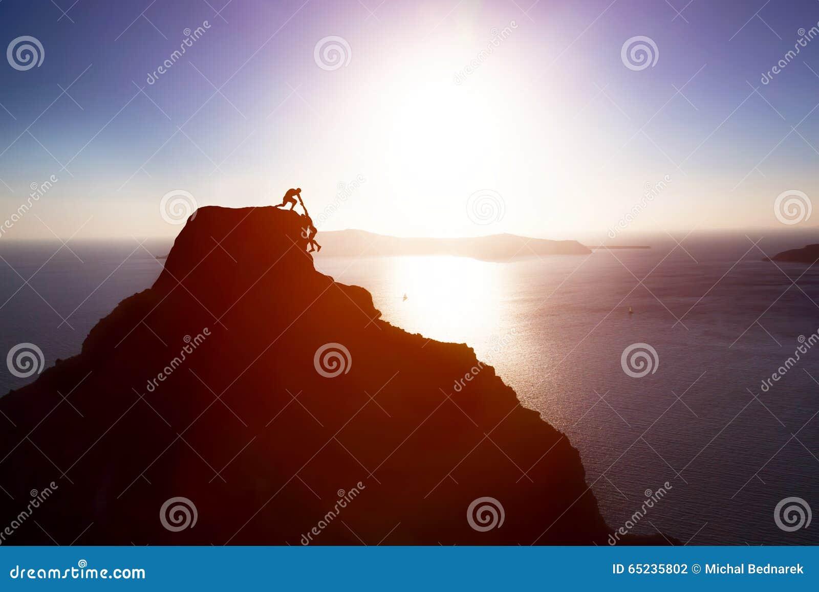Arywista daje ręce i pomaga jego przyjaciela dosięgać wierzchołek góra Pomoc, poparcie