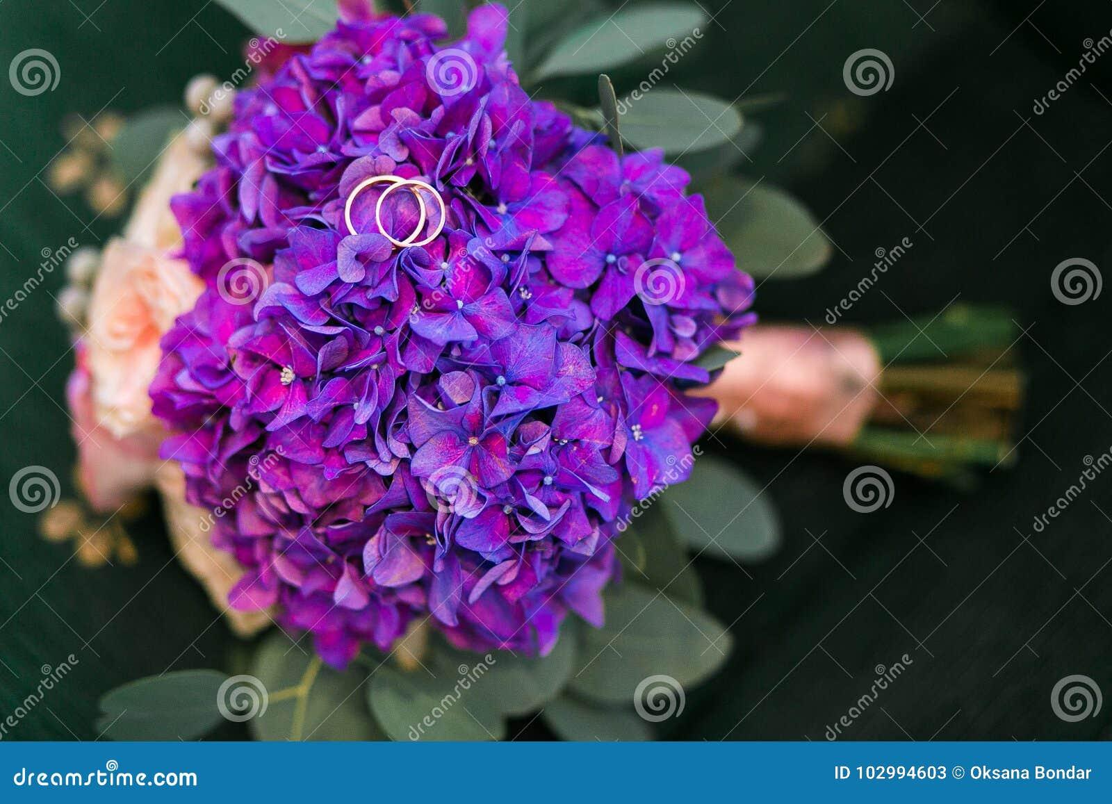 As alianças de casamento douradas no ramalhete da hortênsia roxa, rosas cor-de-rosa florescem com as fitas lilás no estilo rústic