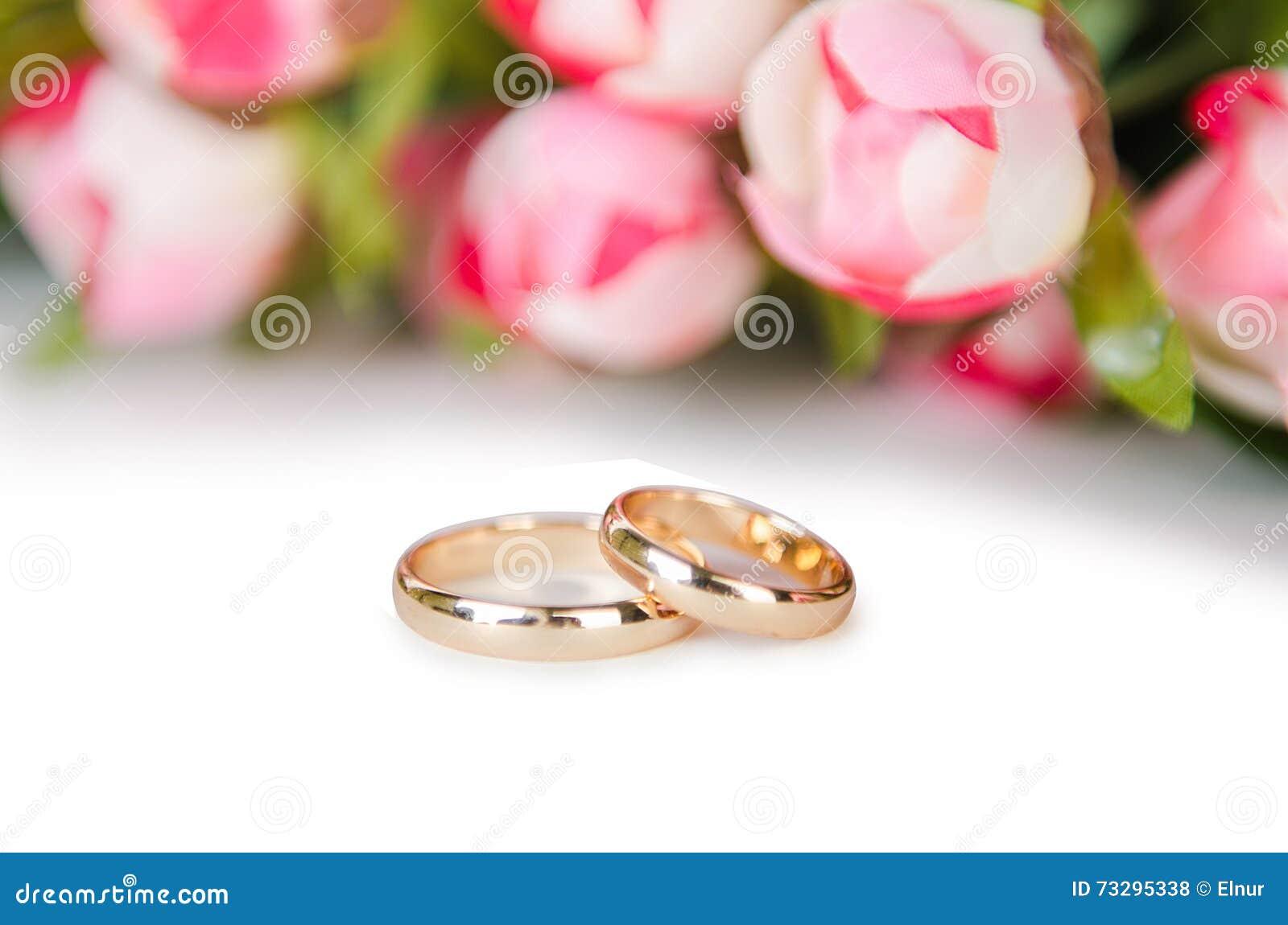 As alianças de casamento e as flores isoladas no fundo branco