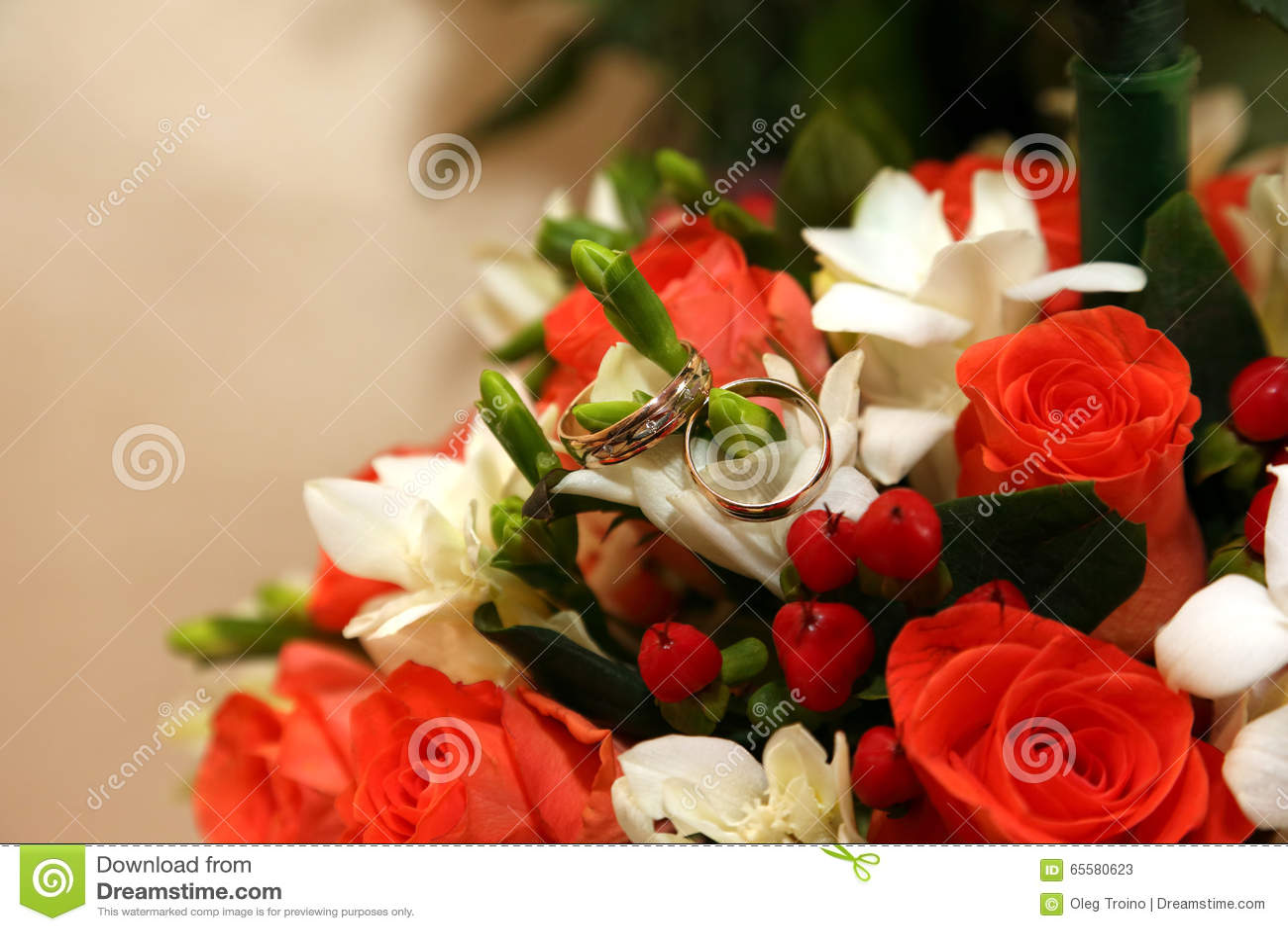 As alianças de casamento encontram-se em um ramalhete da noiva