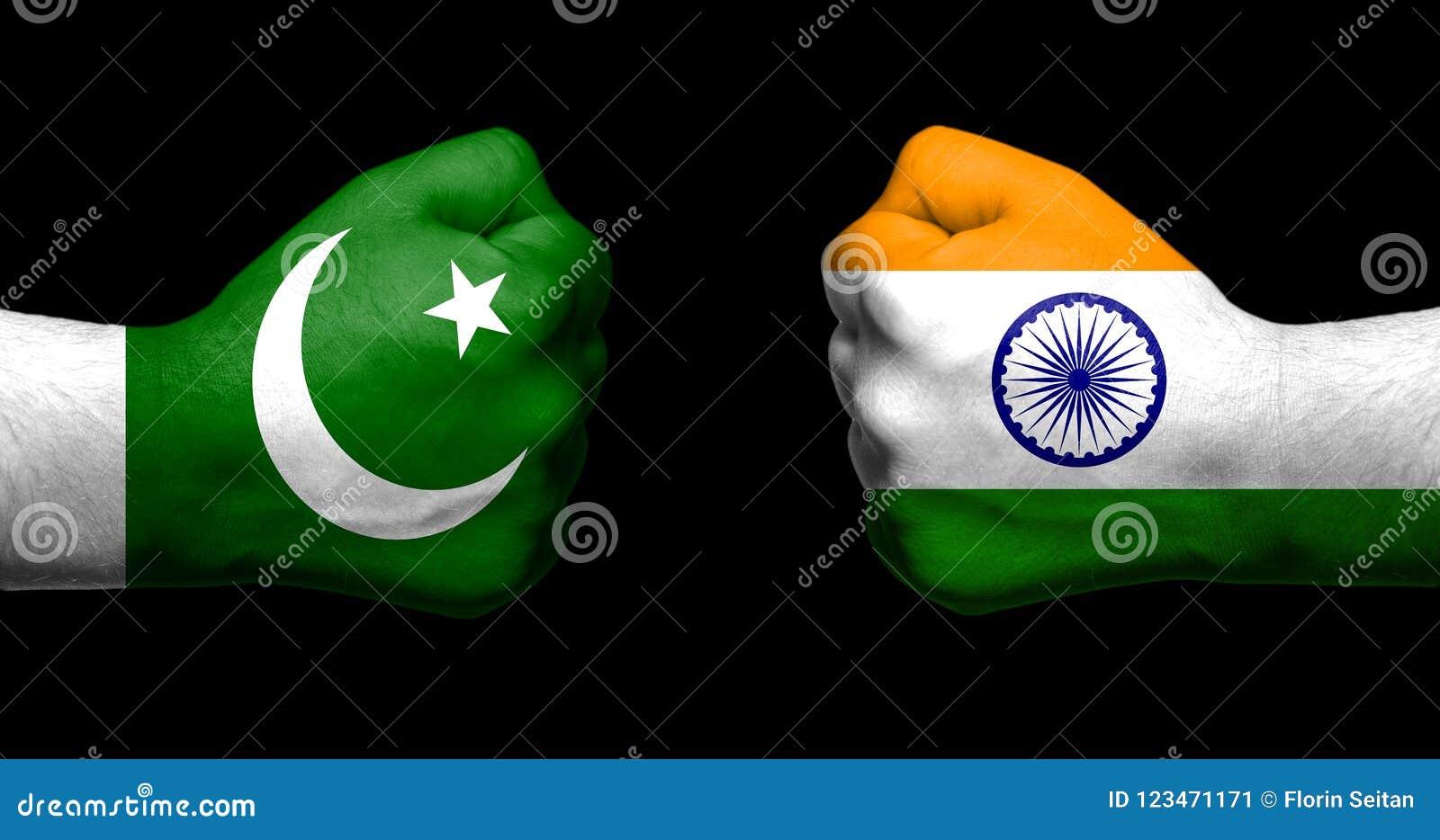 As bandeiras da Índia e do Paquistão pintados em dois apertaram enfrentar dos punhos