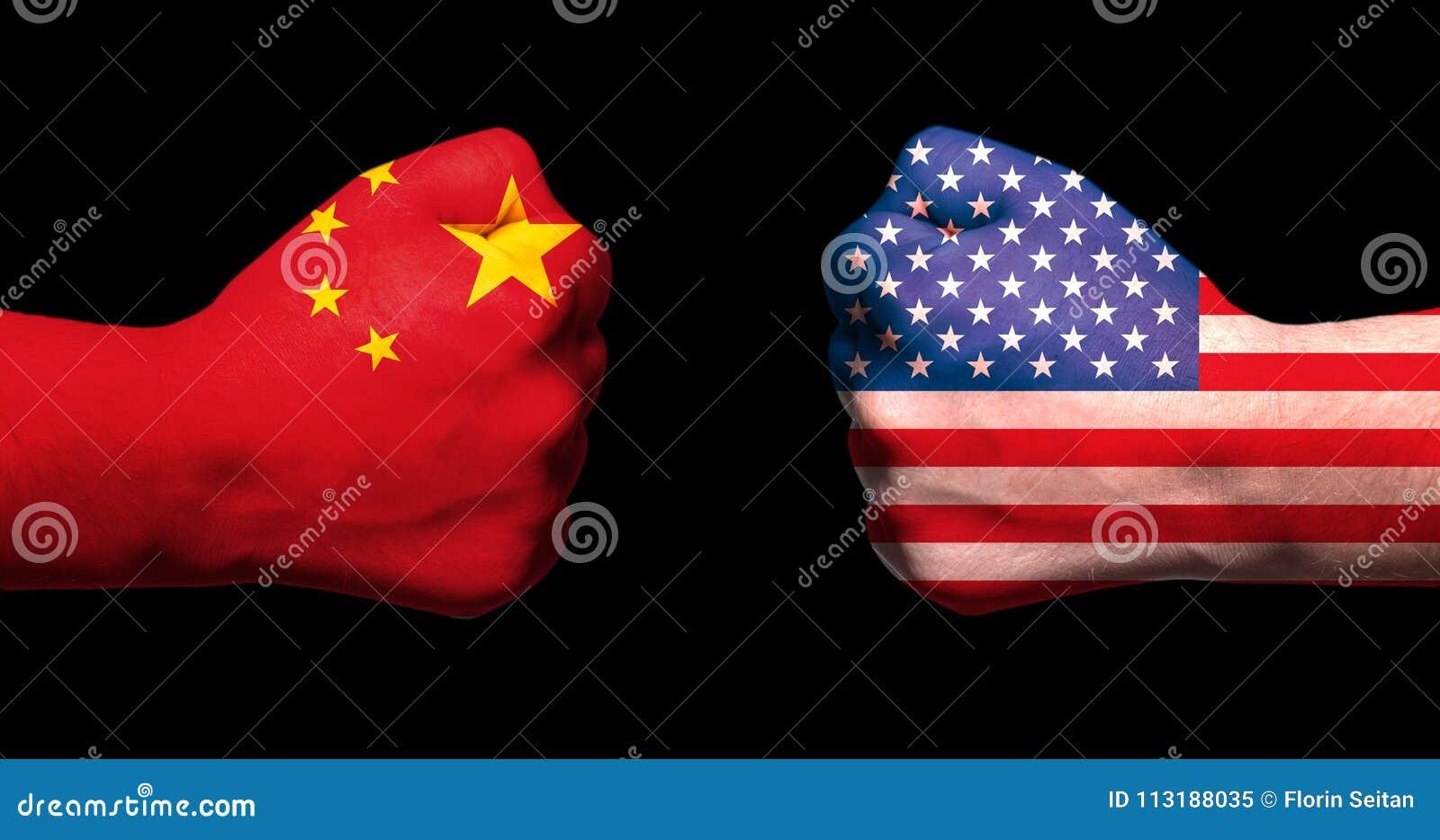As bandeiras dos EUA e da China em dois apertaram os punhos que enfrentam-se no conceito preto da guerra comercial da porcelana d