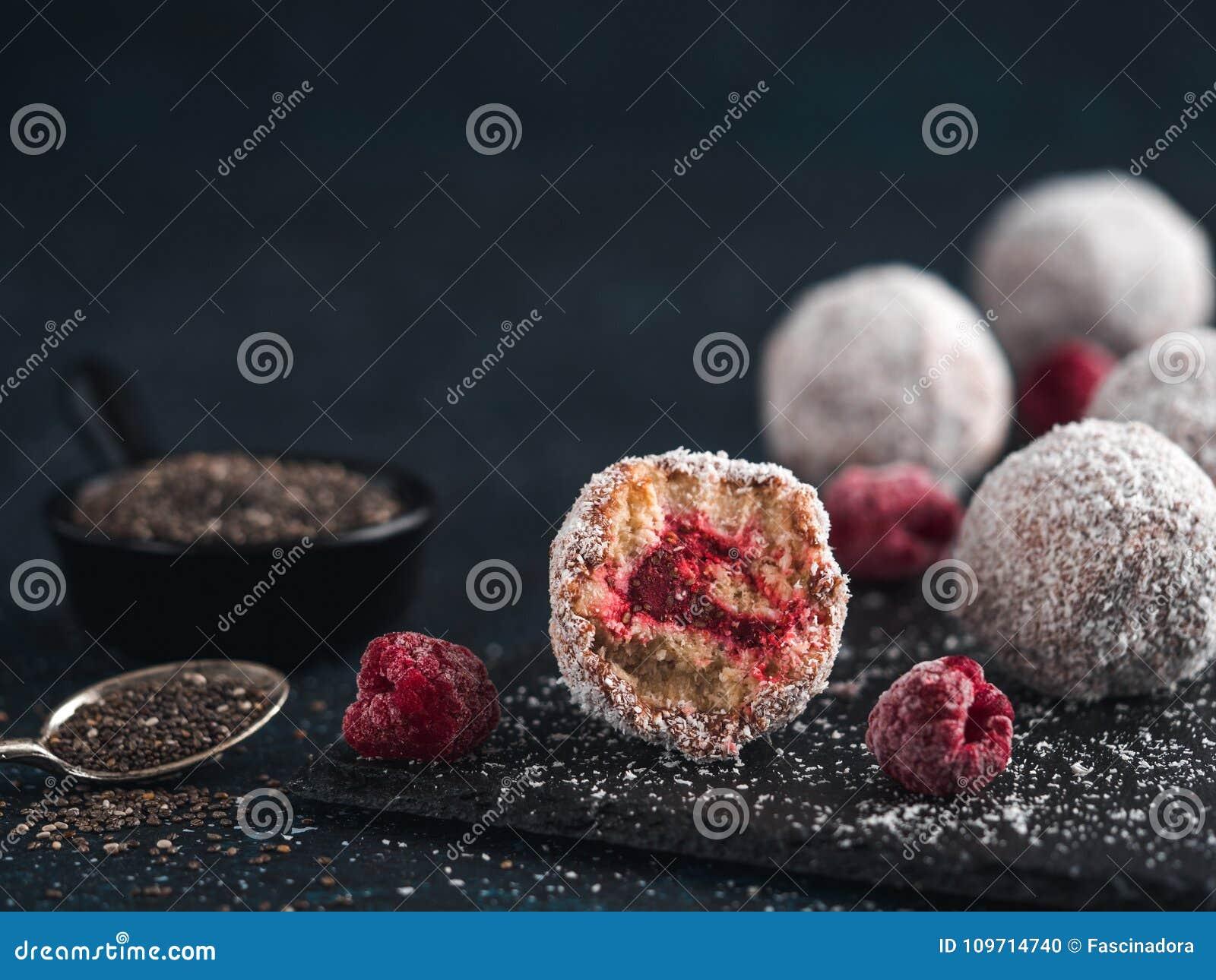 As bolas cruas da felicidade do lamington com chia das framboesas bloqueiam
