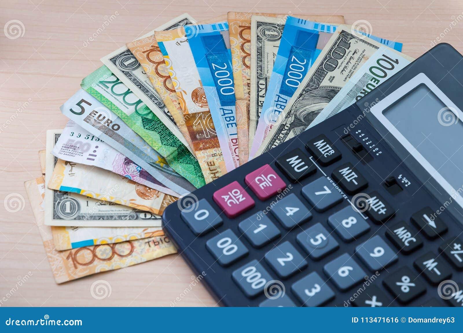 As cédulas diferentes de denominações diferentes são empilhadas em um fã e em uma calculadora na tabela