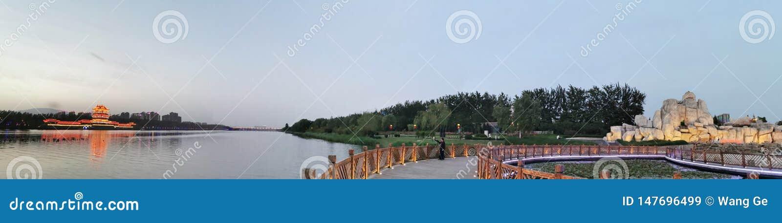 As construções antigas na distância, as madeiras, o jardim ornamental na vizinhança, o lago
