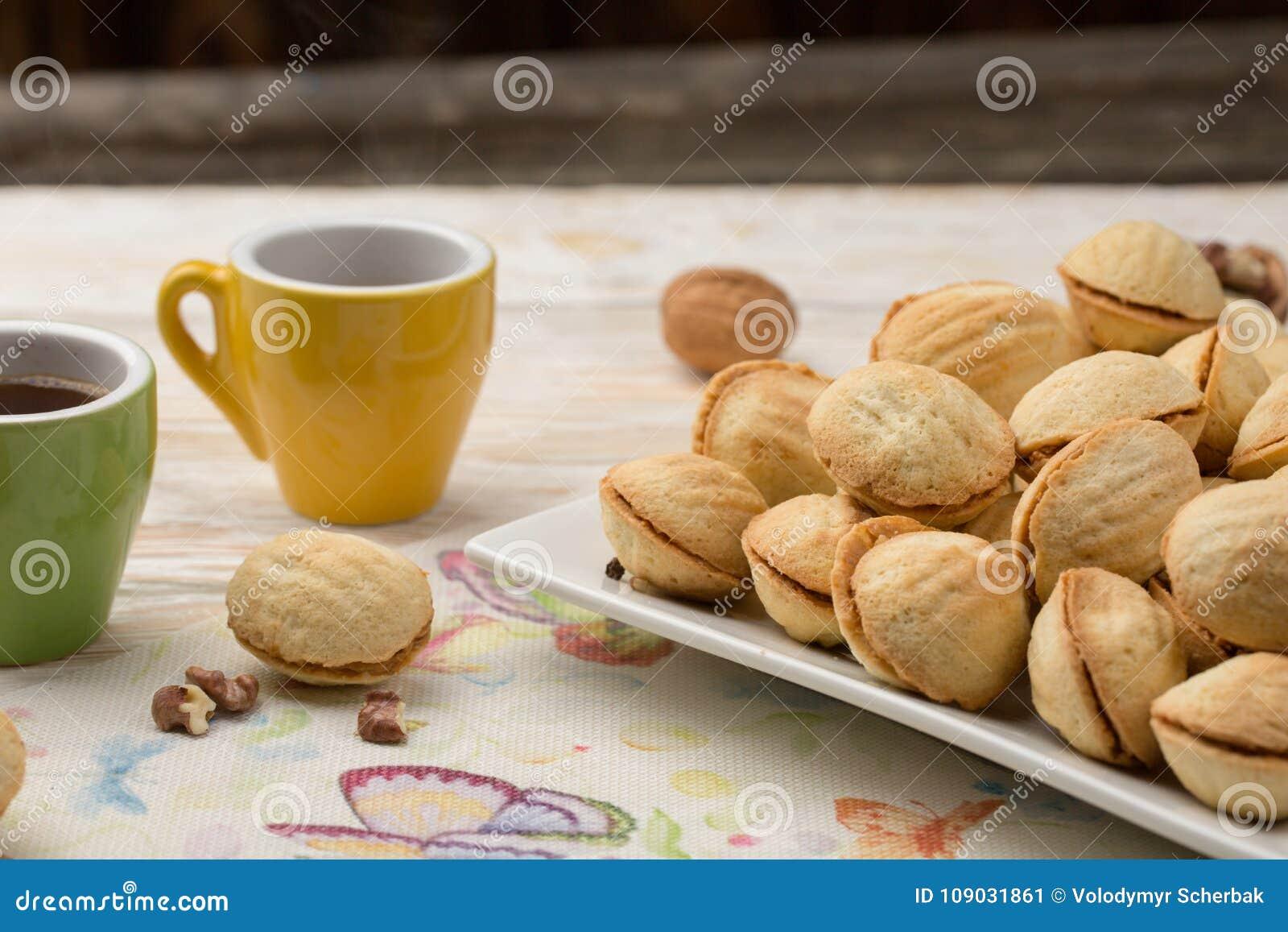 As cookies caseiros deram forma a porcas com leite condensado fervido creme na tabela de madeira