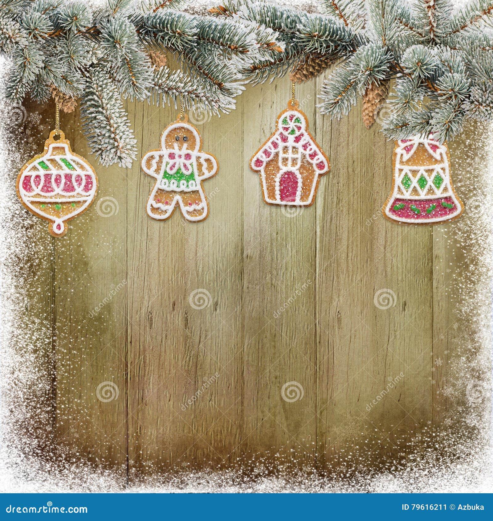 As cookies do Natal, pinho ramificam no fundo de madeira nevado
