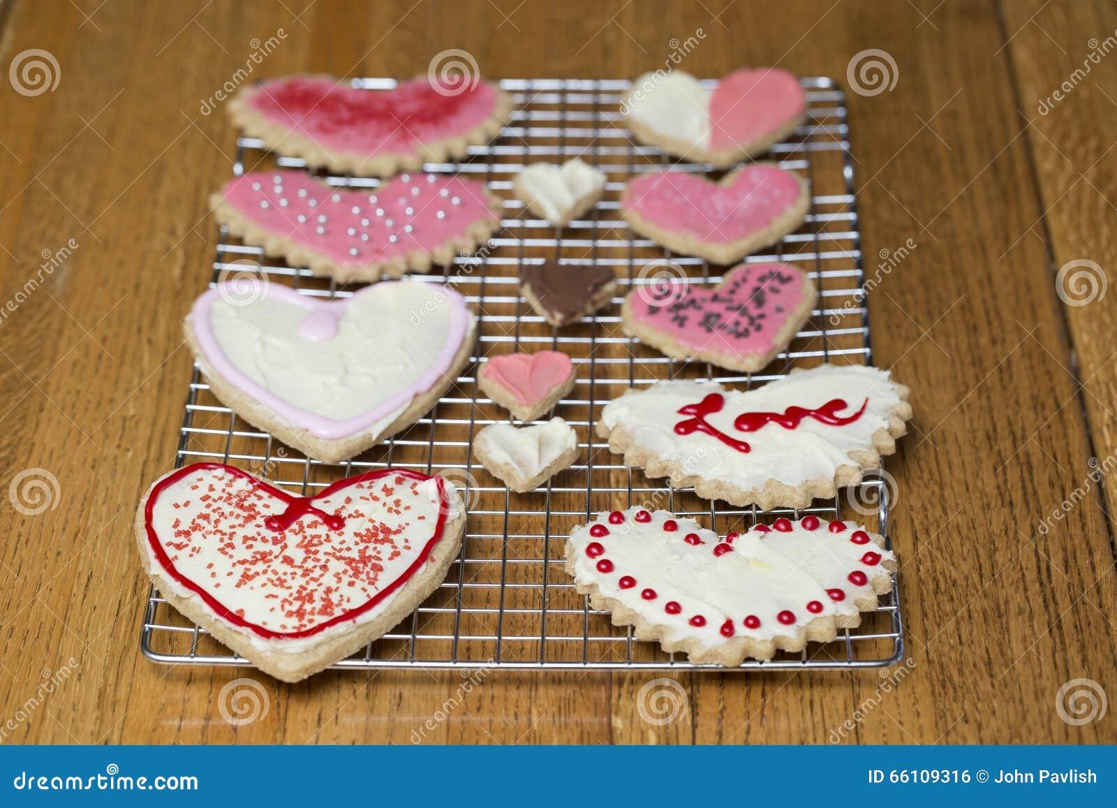 As cookies em ordem do coração do dia de Valentim em uma cremalheira refrigerando ajustaram-se na