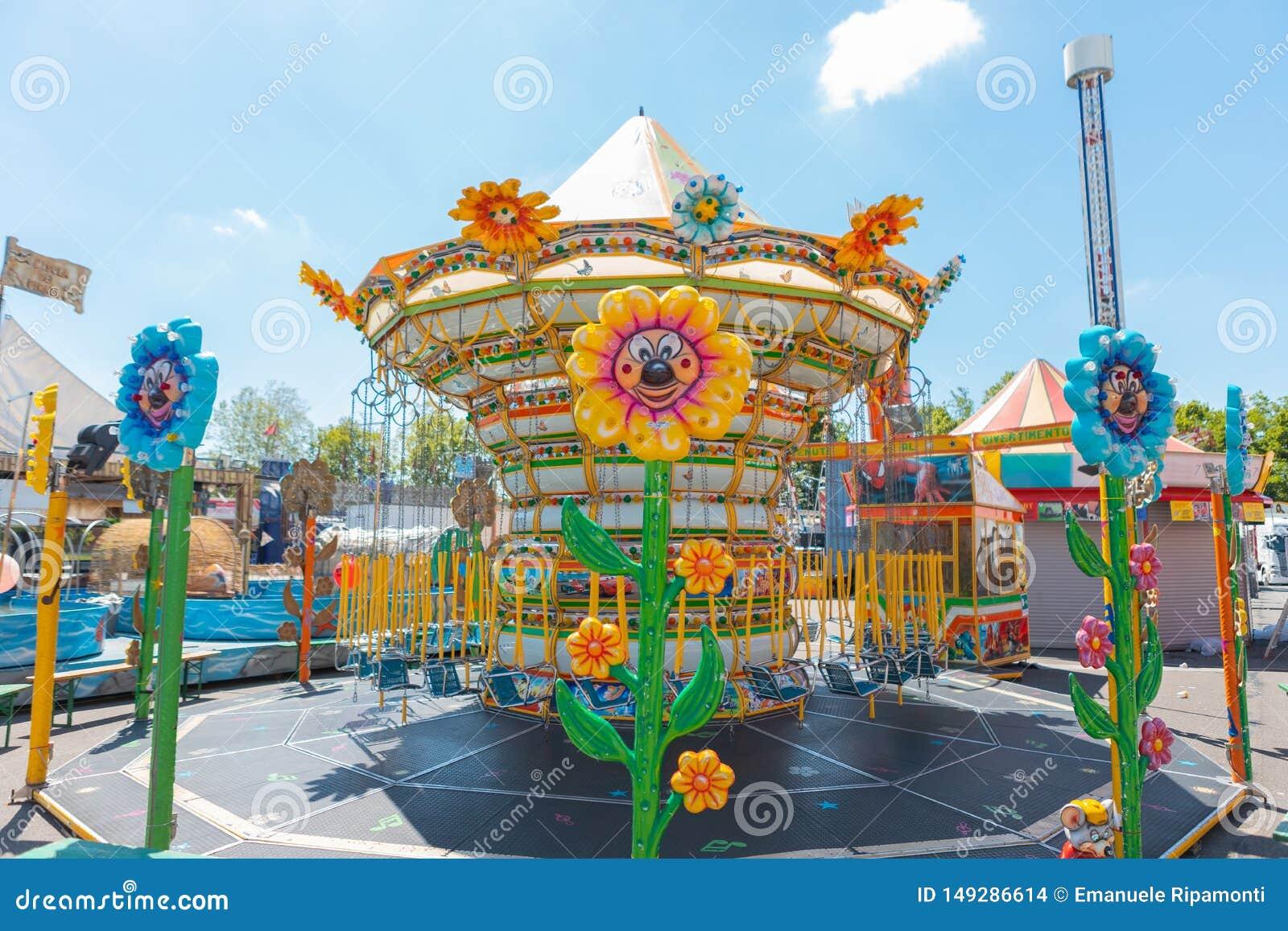 As correntes do carrossel para crian?as em cores brilhantes durante uma feira em uma flor italiana do parque deram forma a luzes