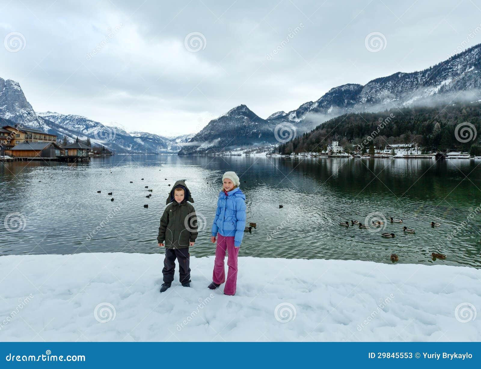 As crianças aproximam o lago alpino do inverno