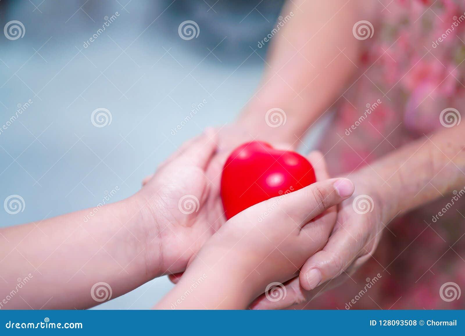 As crianças asiáticas caçoam o toque da posse e dão a coração vermelho a saúde forte às mãos velhas da senhora da mãe com o amor,