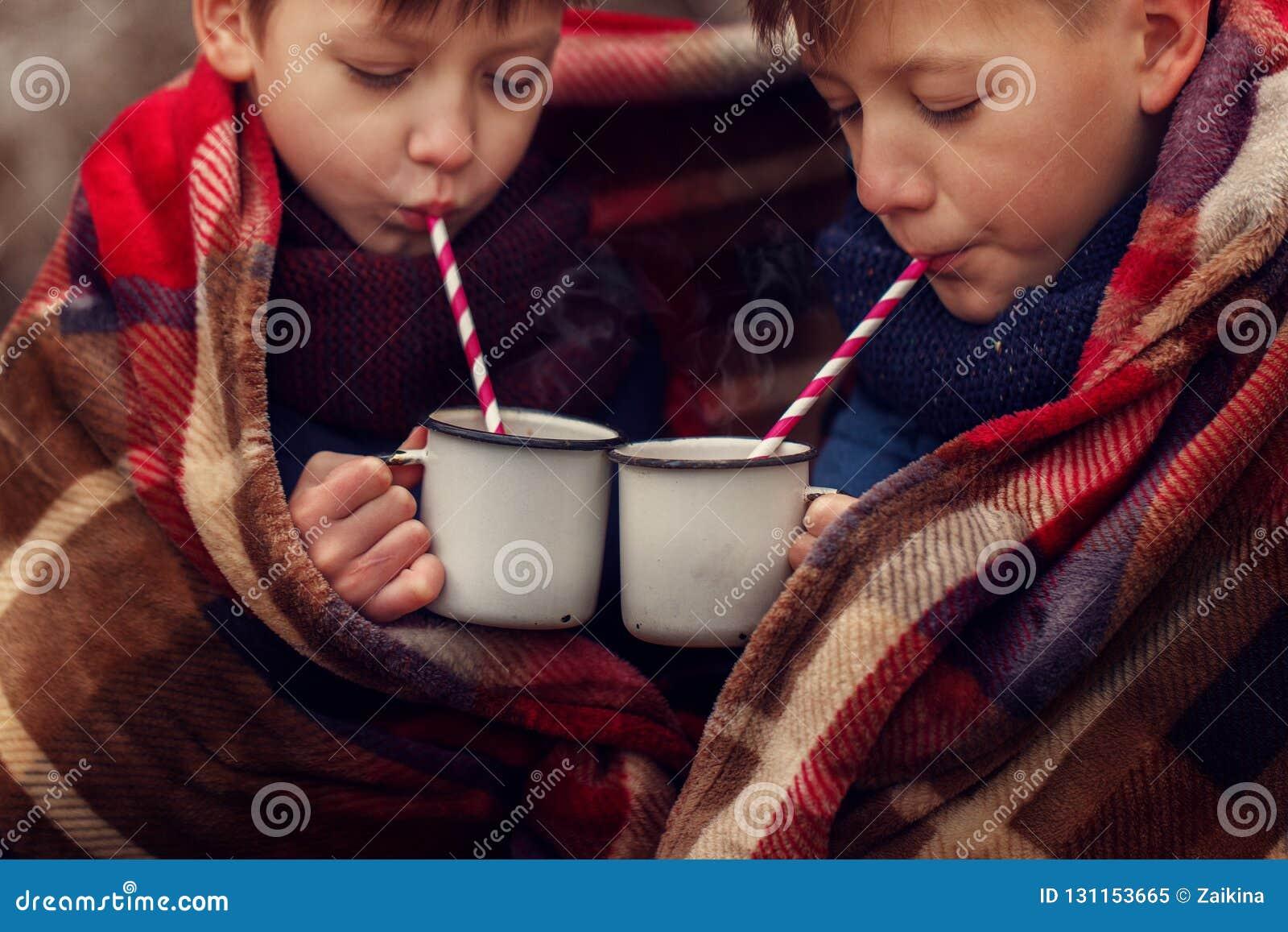 As crianças bebem o chocolate quente sob a cobertura morna em férias do Natal da floresta do inverno