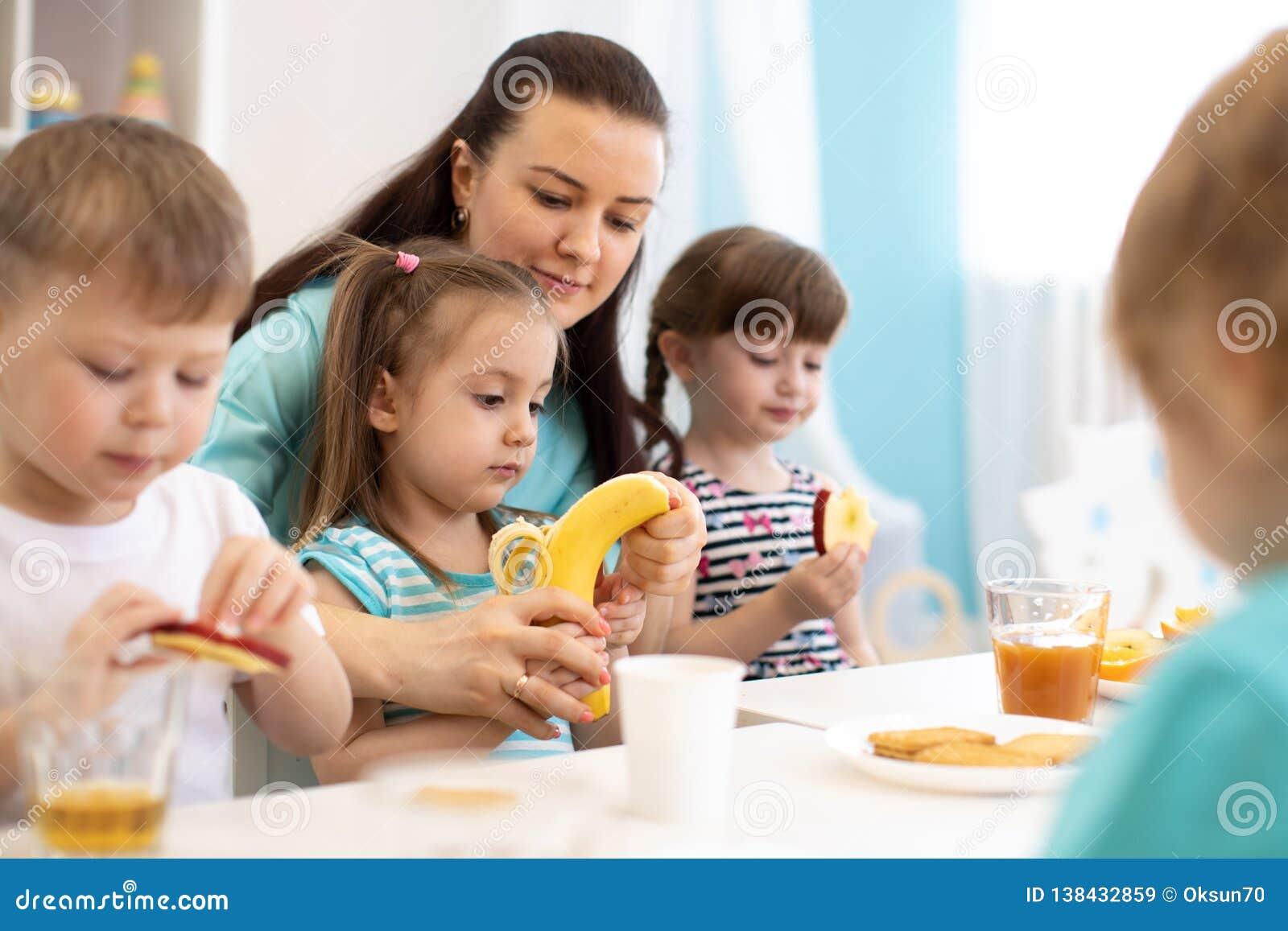 As crianças e a equipe de tratamento comem junto frutos no jardim de infância ou na guarda