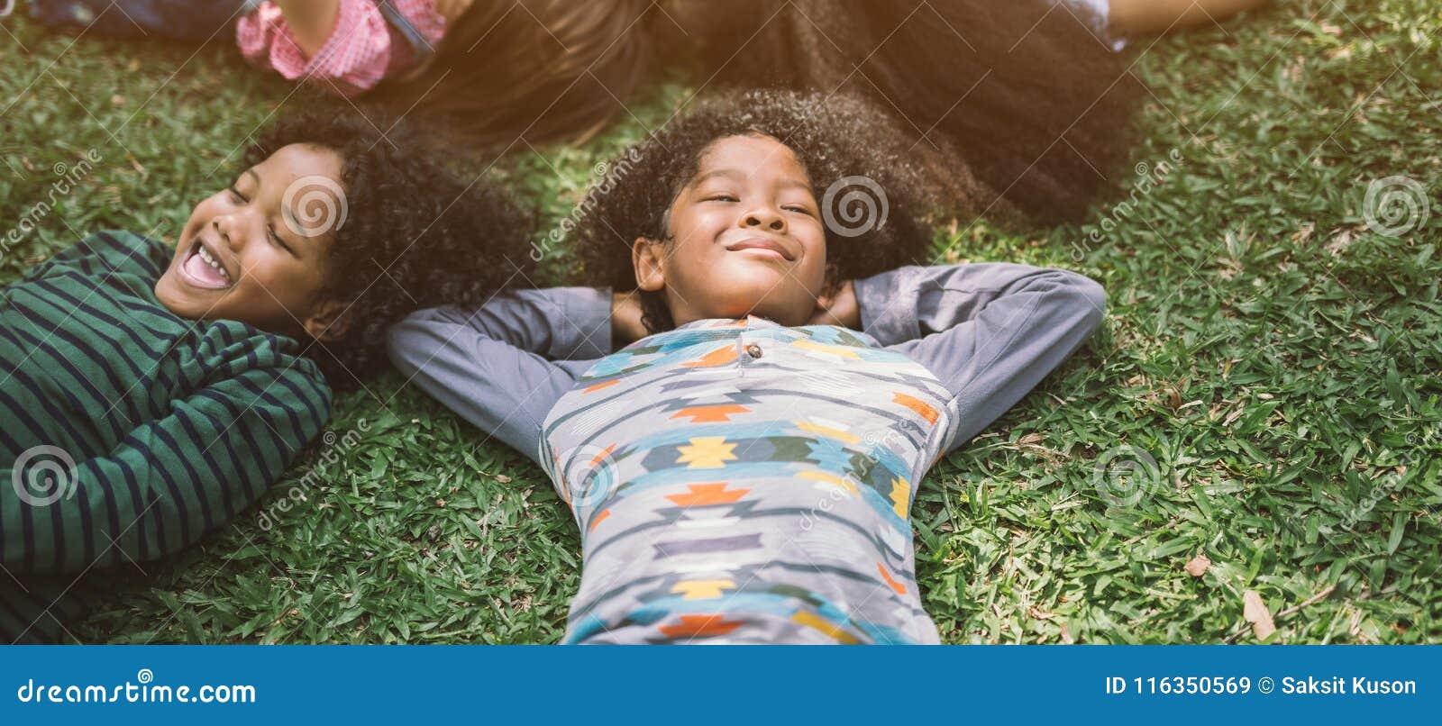 As crianças felizes caçoam a colocação na grama no parque