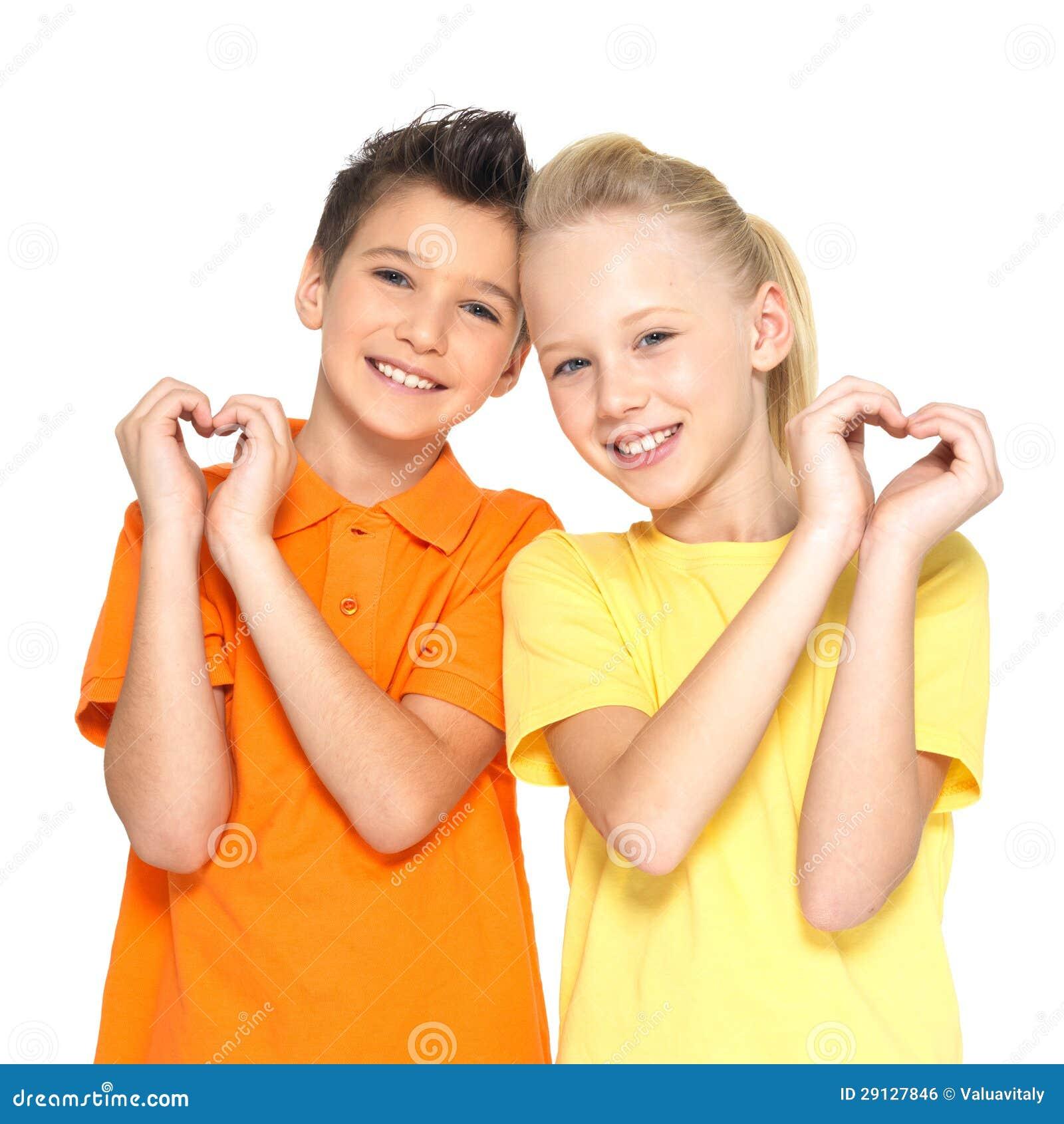 As crianças felizes com um sinal do coração dão forma