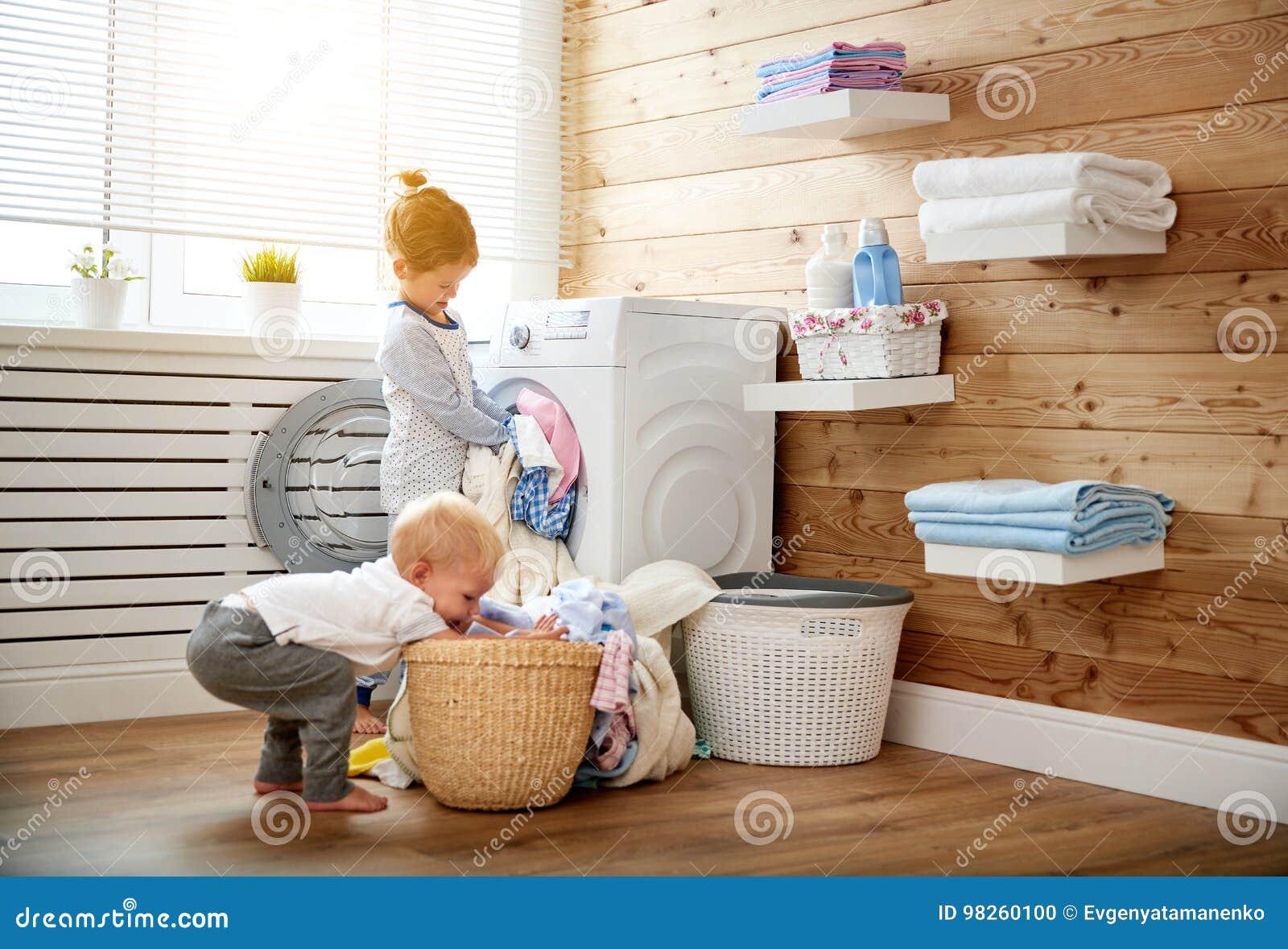 As crianças felizes menino e menina na lavanderia carregam a máquina de lavar