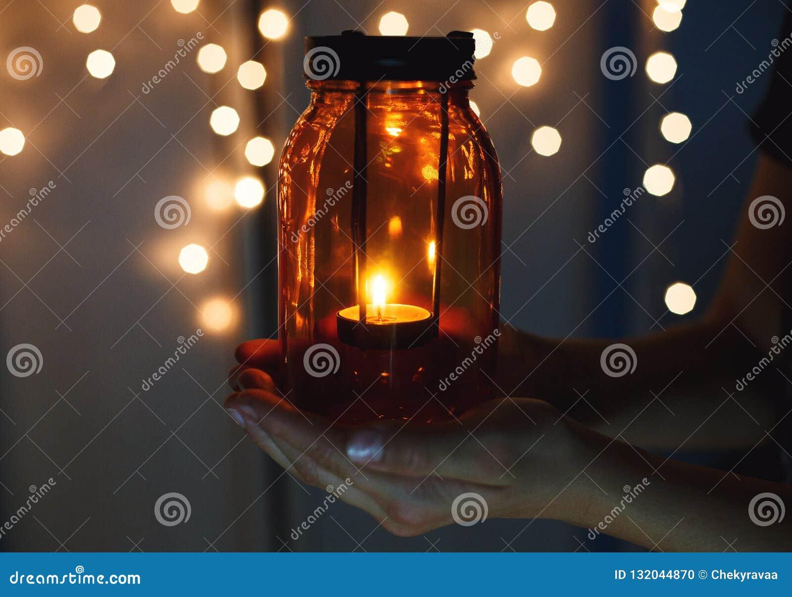 As crianças guardam a lanterna do Natal nas mãos no fundo do bokeh das luzes Conceito da celebração do ano novo, humor festivo