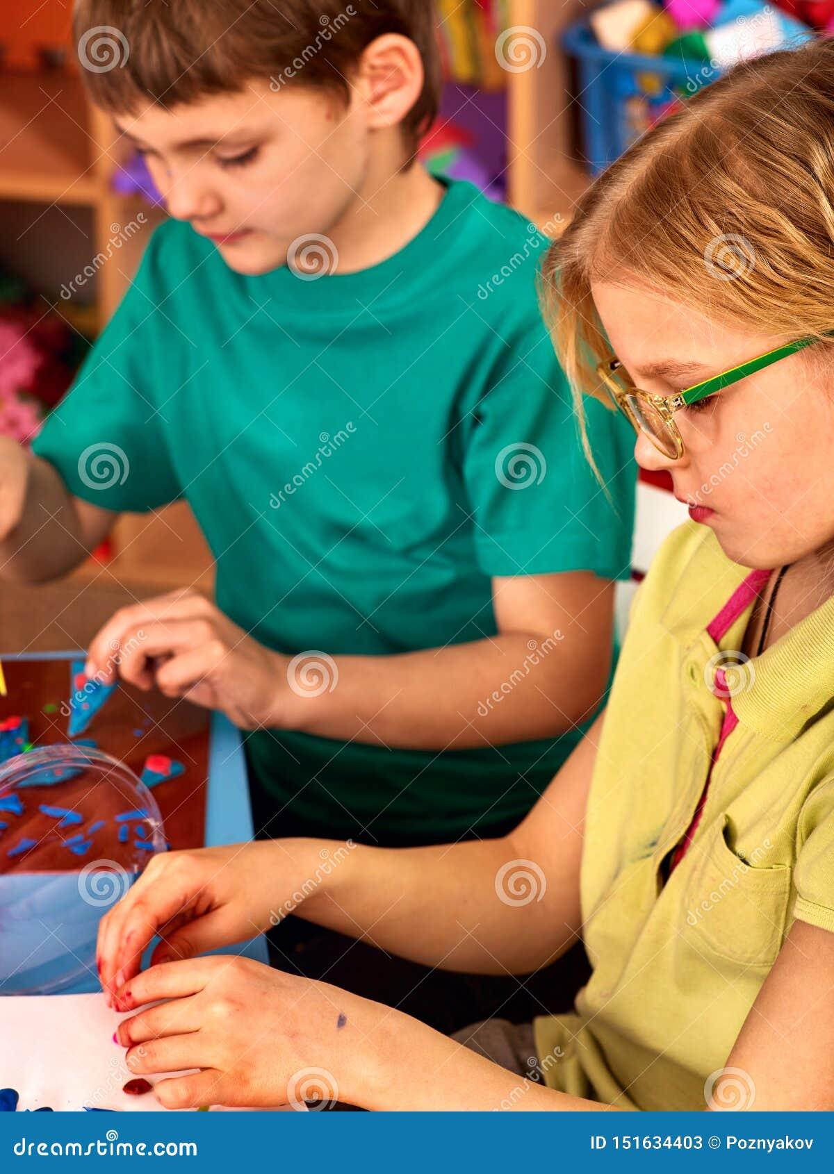 As crianças modelam do plasticine na lição do ofício da escola