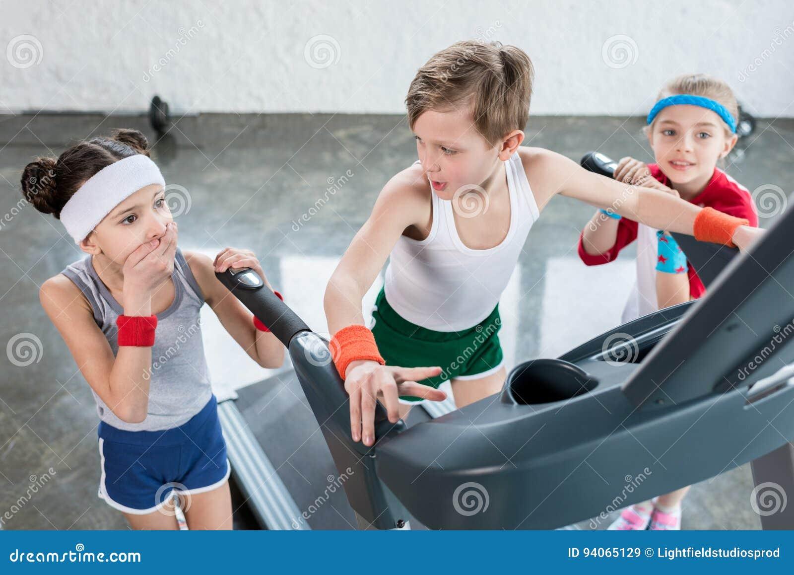 As crianças no sportswear que exercitam na escada rolante no gym, crianças ostentam o conceito da escola