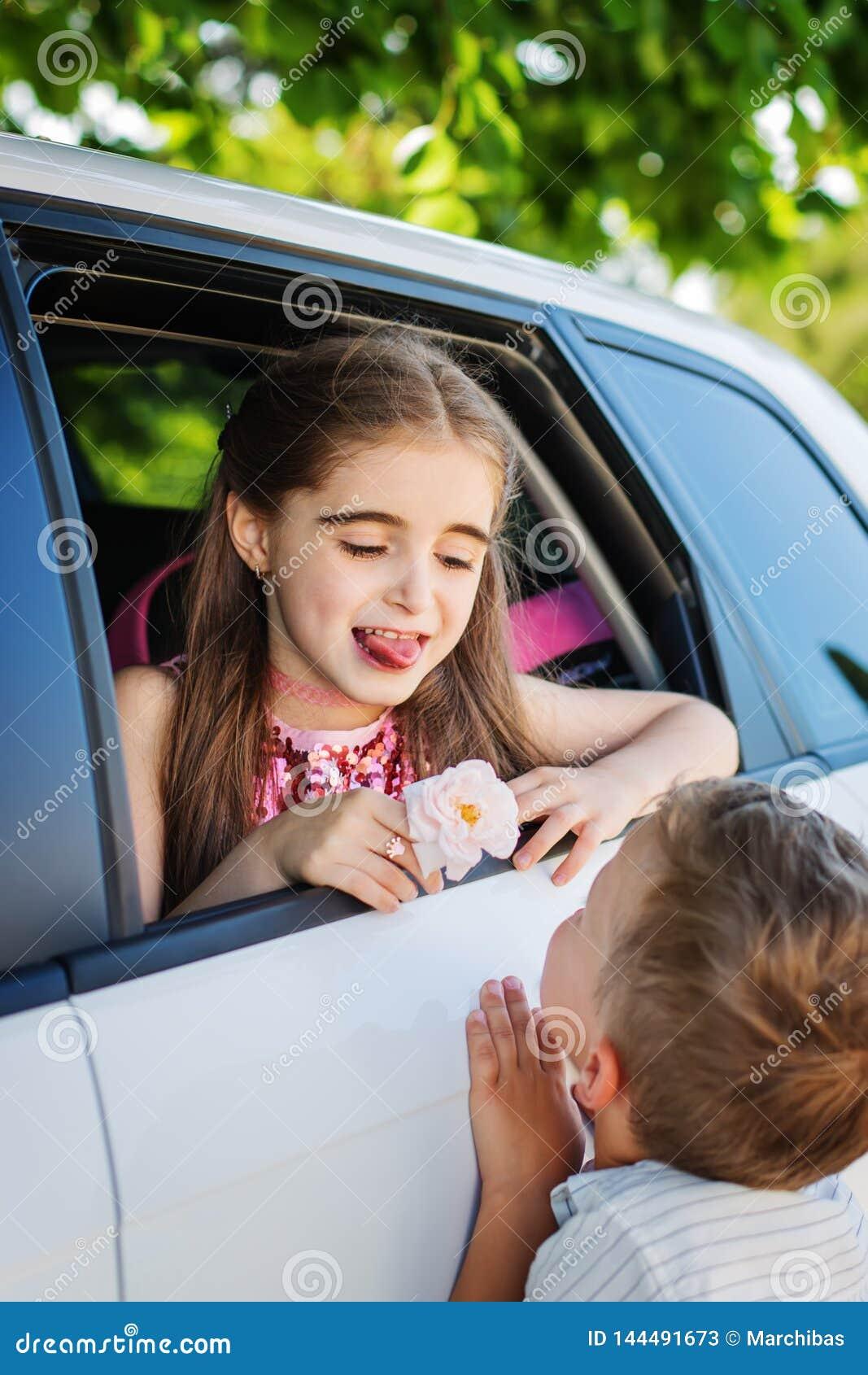As crianças pequenas jogam, menino dão a uma menina uma rosa