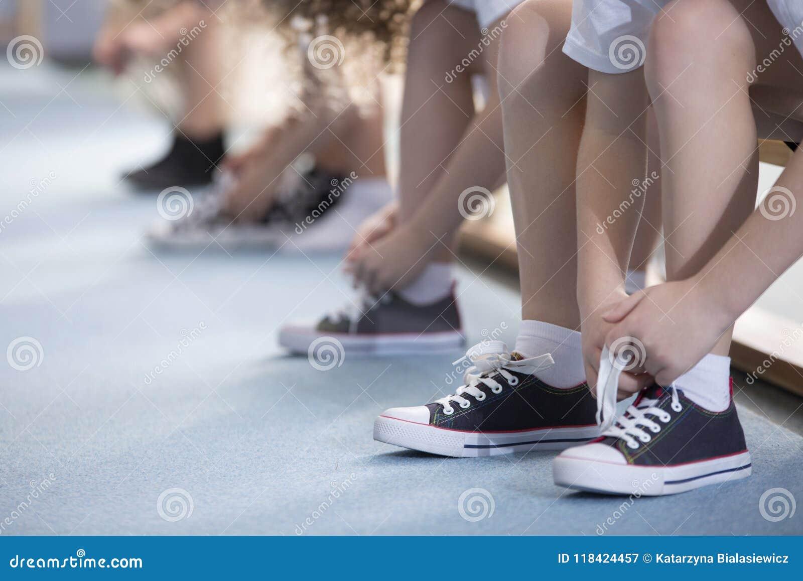 As crianças que amarram o esporte calçam o close-up