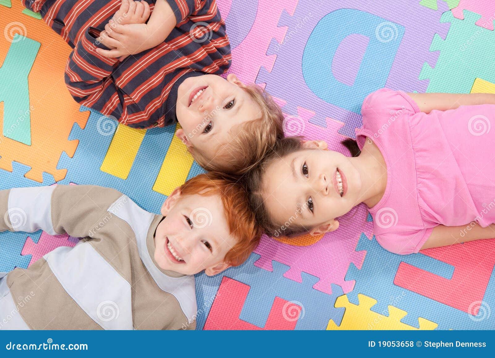As crianças que encontram-se nas partes traseiras no divertimento caçoam a esteira do alfabeto