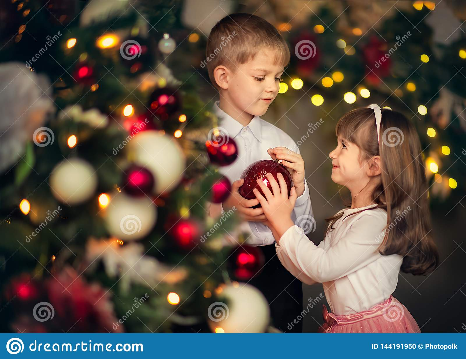 As crianças vestem acima uma árvore de Natal