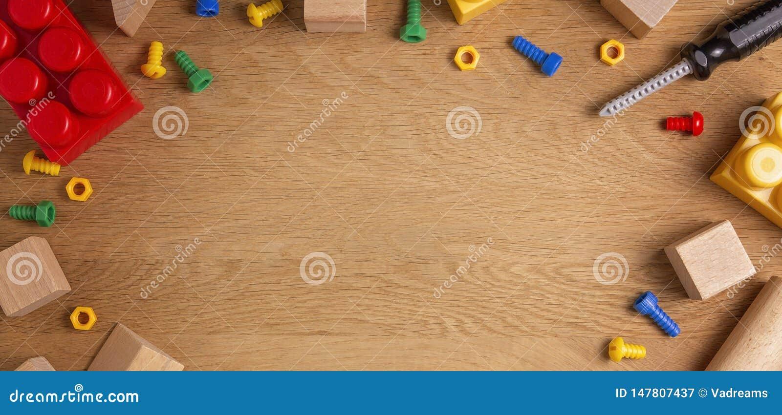 As crian?as brincam o fundo do quadro com ferramentas, blocos e cubos do brinquedo na tabela de madeira Vista superior