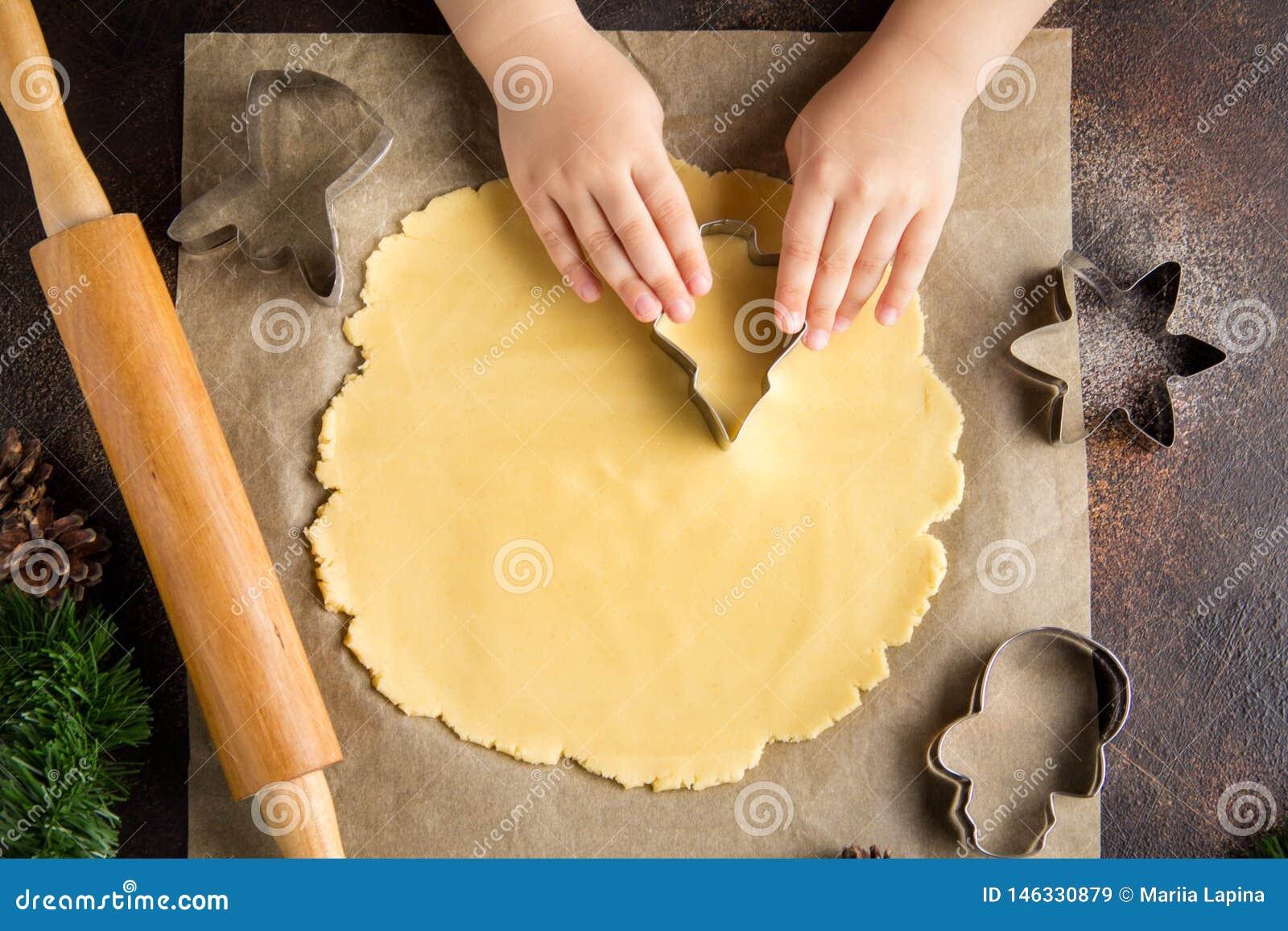 As crian?as que cozinham cookies do Natal, cortaram a massa com cortador da cookie, tradi??es da fam?lia, alimento doce delicioso